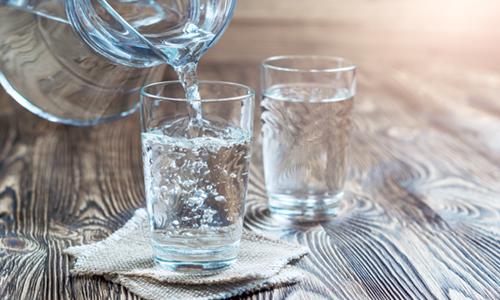 bild på en tillbringare som häller vatten i två glas på ett bord