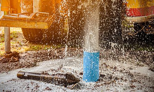 bild som visar sprutande vatten ur slang och borrkax på marken